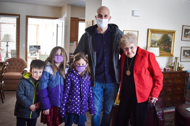 Pastor Ryan Morter and his children, from left, Dean, Myra and Vivian, spent Sunday afternoon delivering Valentine's Day gifts to widows and widowers to remind them they are loved. Here, they are delivering a gift basket and a blanket to Geri Chisholm in her Marblehead home.