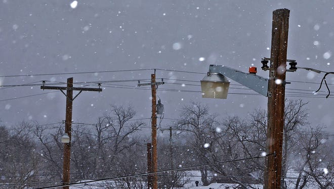 Snow falls over utility lines in San Angelo on Sunday, Feb. 14, 2021. A winter storm over the weekend resulted in widespread power disruptions and rolling blackouts.