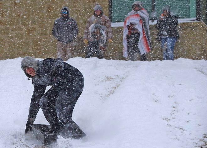 Jake Amerman, far left, sleds down a hill near the riverwalk in downtown San Angelo on Sunday, Feb. 14, 2021.