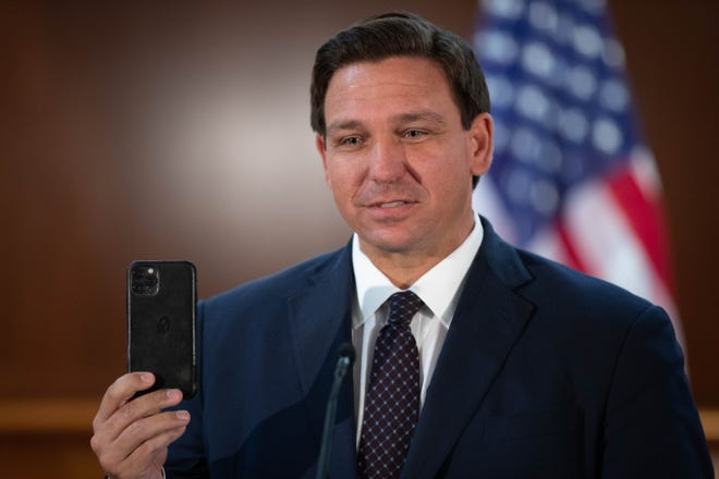 Gov. Ron DeSantis holds up his iPhone as he begins a press conference discussing the Transparency in Technology Act at the Capitol Monday, Feb. 15, 2021.