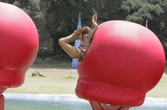 "A muddy ""Wipeout"" contestant collides with a bouncy, red structure."