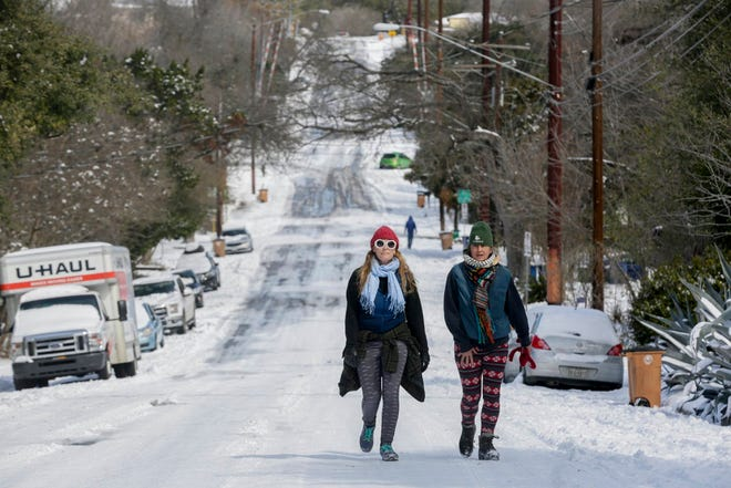 Tina Martinez (left) and Kristie Kittrell walk up Cherrywood Road in Austin on Tuesday.