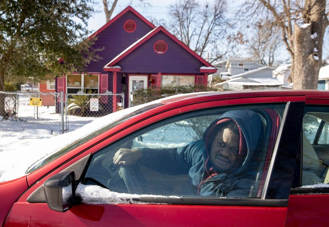 Isaiah Buckram sits in his car to warm up outside his home on Garden Street in East Austin on Tuesday February 16, 2021, during a power outage caused by a winter storm. Buckram said his home has been without power since early Monday morning.