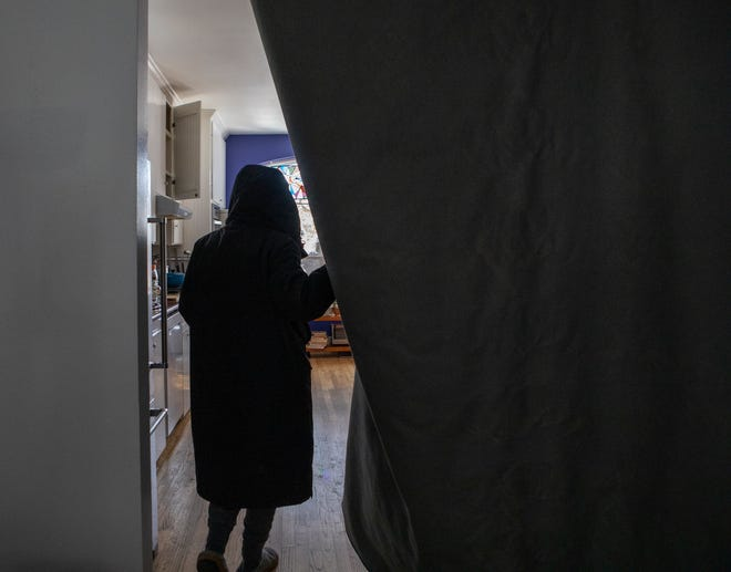 Deborah Byrd is shown during the February freeze walking past a rug she hung between her living room and kitchen in an attempt to keep her home warmer during the prolonged power outage.