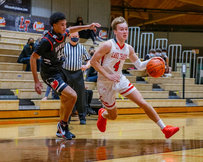 Lake Travis guard Bennett Moore drives to the basket while guarded by Bowie guard L.D. Butler in a District 26-6A game last month. Lake Travis will enter the playoffs as the district's third seed and will face Hutto in a bidistrict game later this week.