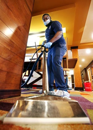 Antonio Goodwin, owner of A Better Cleaning Service, cleans the carpets in the main lobby of the Fairfield Inn off Arlington Road.