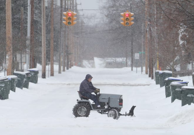 "Jerry Wittman plows neighbors driveways on Monroe Avenue on Tuesday, Feb. 16, 2021 in Cuyahoga Falls, Ohio. ""I just do my thing to help out,"" said Wittman. [Phil Masturzo/ Beacon Journal]"