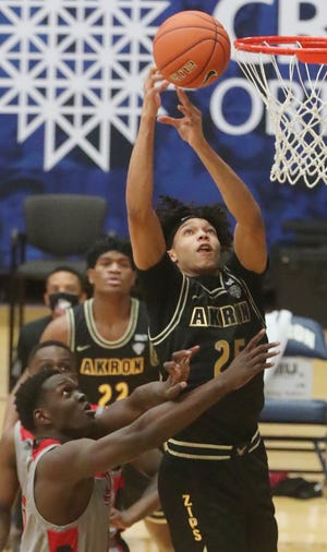 University of Akron forward Enrique Freeman goes for a rebound against Northern Illinois' Adong Makuoi in a game earlier this week at Rhodes Arena. [Mike Cardew/Beacon Journal]