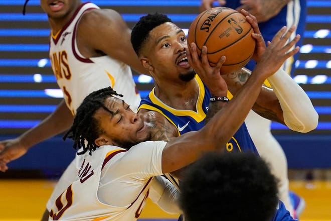 Golden State Warriors forward Kent Bazemore, right, shoots against Cleveland Cavaliers guard Darius Garland during the first half of an NBA basketball game in San Francisco, Monday, Feb. 15, 2021. (AP Photo/Jeff Chiu)