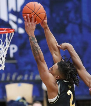 University of Akron forward Cameron Reece shoots over Northern Illinois' Justin Lee during the Zips' 81-76 win Tuesday afternoon at Rhodes Arena. [Mike Cardew/Beacon Journal]
