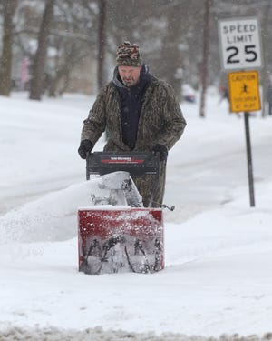 Mike Schustrich plows his sidewalks on Adaline Drive on Tuesday, Feb. 16, 2021 in Stow, Ohio. [Phil Masturzo/ Beacon Journal]