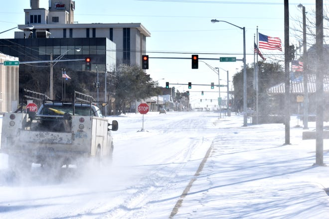 A vehicle travels down a snow-covered West Main Street Monday, Feb. 15, 2021.