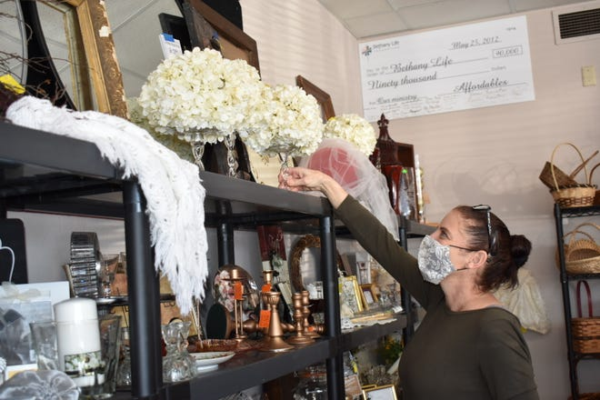Manager Natalie Johnson arranges a bridal display at Affordables in Story City. In the background is one of the many large checks on display -- this one for $90,000 -- that are donated to Bethany Life to help the residents there.