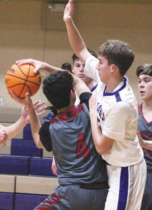 Wesleyan Christian School's Tyrel Cloud, right, looms over an opposing shooter during varsity boys basketball action this season.