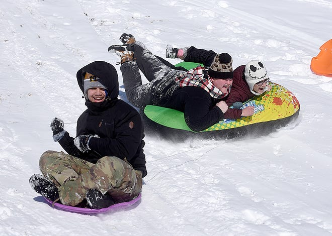 Corban Payne, 15, left, slides down a hill alongside Kelly Smith, center, and Michelle Pulis on Tuesday at Cosmo-Bethel Park. The city has opened Cosmo-Bethel Lake to ice fishing and Stephens Lake Park to ice skating.