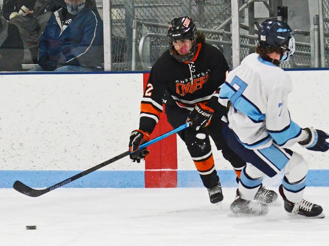 Cheboygan junior forward Jakob Heilman (left) looks to keep control of the puck in front of Petoskey's Ethan Decker (7) during a hockey matchup in Petoskey on Monday.