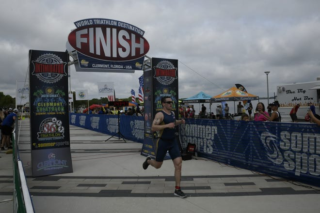 A competitor crosses the finish line at the 2019 Great Clermont Triathlon. The event was canceled last year because of the COVID-19 pandemic.