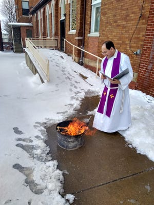 Father Paul Hrezo of Christ Our Light Parish conducts the burning of the blessed palm branches for making the ashes that will be used for Ash Wednesday Masses.