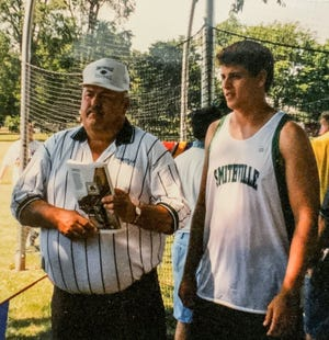 Sam Sayre coaches Zach Carr, a state champion for Smithville in the discus. Sayre played three sports for the Smithies during his playing days and coached multiple sports during his life.