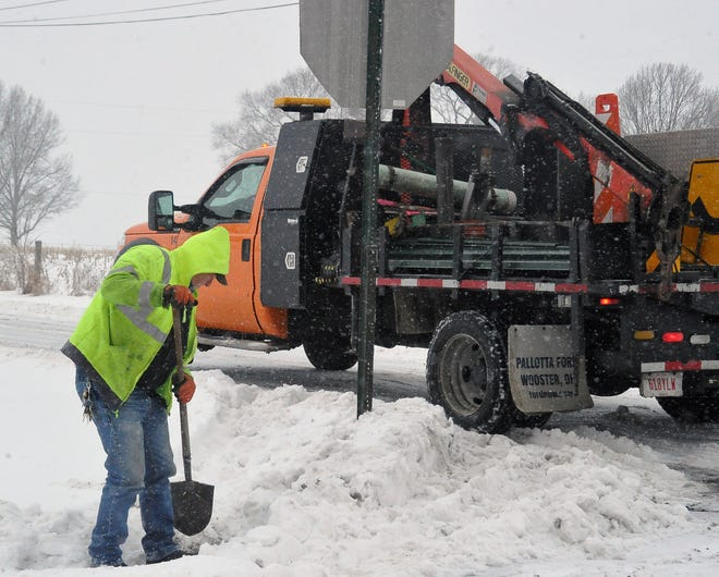 Jeff Metcalf of the Wayne County Sign Shop fixes a stop sign on County Road 501 that had been run over by a semi during the Tuesday winter storm.