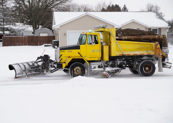 A snowplow clears a road Tuesday in Adrian Township. A snowstorm that began Monday evening and continued into Tuesday morning dumped more than half-a-foot of snow on most of Lenawee County.