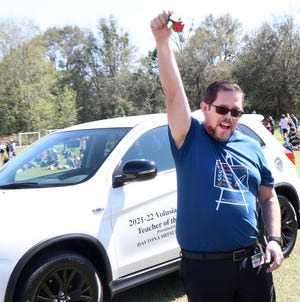 Citrus Grove Elementary School art teacher Frank Garaitonandia, the Volusia County Teacher of the Year, lets out a cheer as he holds high the keys to a new car, he'll drive for a year, Tuesday February 17, 2021 during a presentation at the school in DeLand.