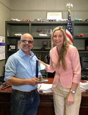 Ascension Economic Development Corporation President and CEO Kate MacArthur presents former Donaldsonville City Council member Brent Landry with an appreciation plaque.