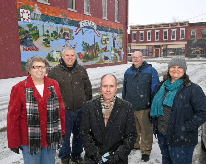Shown Monday near a mural, just off Main Street West in Girard, that celebrates the history of the west Erie County municipality are, from left: Borough Councilwoman Jeanne Miller, Downtown Girard committee member Jim Tometsko, committee chair George Drushel, Borough Manager Rob Stubenbort and Melinda Meyer of Preservation Erie, who is helping the committee with a project to seek Downtown Historic District designation from the National Register of Historic Places for 1.5 miles of West Main Street.