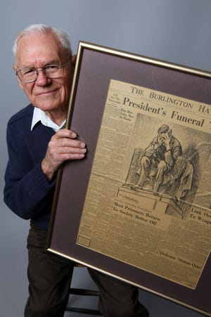 Bob Sogard of Burlington remembers the assassination of President Kennedy from the workings of The Hawk Eye newsroom while holding a paper from that time Dec. 10, 2014, in Burlington. He worked in various reporting roles from 1953-1986, ending his career covering agriculture.