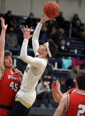 Notre Dame High School's Matthew Johnson (3) puts up a shot over Bryce Wade (45) during their District 8 quarterfinal game against Winfield-Mount Union Monday Feb. 15, 2021 at Notre Dame's Father Minett Gymnasium.