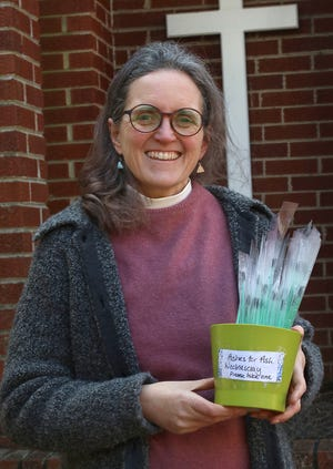 The Rev. Caroline Kramer holds a bucket of ashes for Ash Wednesday on Tuesday. Those who want to take part in Ash Wednesday can find the ashes outside Episcopal Church of the Redeemer on West Sumter Street in Shelby.