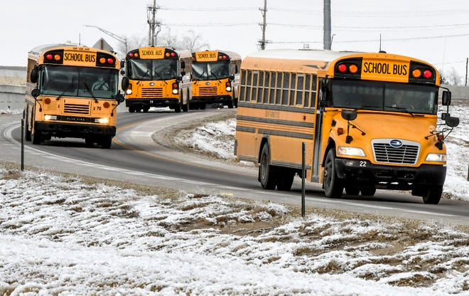 A group of school buses for USD 457 head along a US Highway 83/50 Bypass exit ramp Thursday after picking up Garden City High School students at the end of the school day.