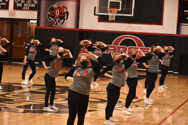 Orion High School cheerleaders perform at the season-opening boys basketball game with Riverdale on Tuesday, Feb. 9, in the Charger gym. In the weeks before the season, state officials had determined cheerleaders could not be in the gym because of COVID-19 restrictions. They were happy to find out the rules had changed and they could cheer on the sidelines and on the floor.