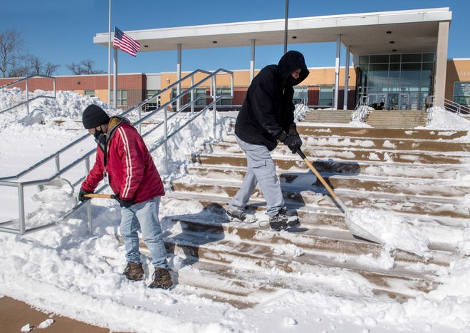 Peoria Public Schools District employees Guillermo Gonzalez, left, and D.J. Richardson Sr. work Tuesday on shoveling snow off a set of concrete steps in front of Harrison Community Learning Center in Peoria.