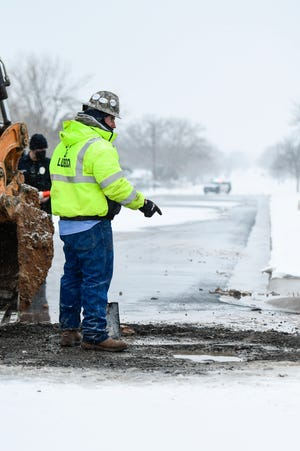 A city worker works to stop a water leak after a fire hydrant was hit at 42nd Street and Avenue U on Tuesday, Feb. 16, 2021, in Lubbock, Texas. [Justin Rex/For A-J Media]