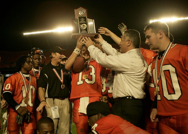 Lakeland quarterback Billy Lowe receives the championship trophy from an FHSAA official at Dolphins Stadium after the Dreadnaughts defeated St. Thomas Aquinas 39-10 in the 2005 Class 5A state championship game. Lowe's play at quarterback gave the Dreadnaughts a dangerous passing game to go along with 1,000-yard rushers Chris Rainey and Jamar Taylor.