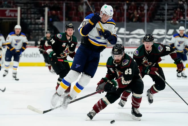 Arizona Coyotes right wing Conor Garland (83) shields St. Louis Blues center Oskar Sundqvist (70) from the puck in the first period during an NHL hockey game, Monday, Feb. 15, 2021, in Glendale, Ariz.
