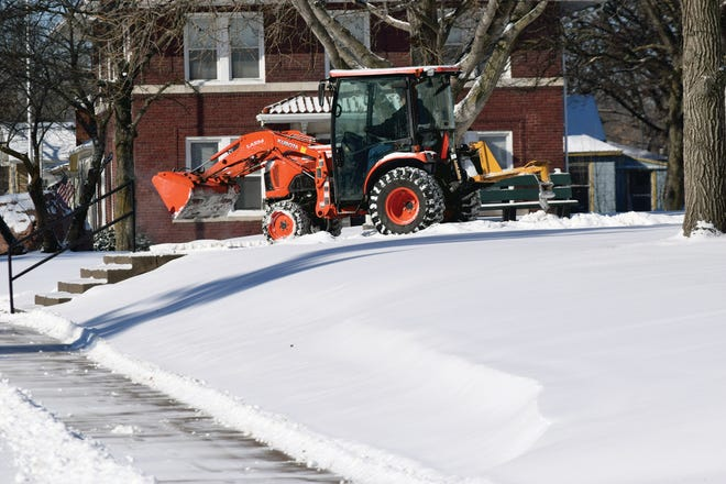 Snow is cleared from areas around the Leavenworth County Courthouse on Tuesday. Most county officers were closed Tuesday because of the weather and potential for rolling blackouts.