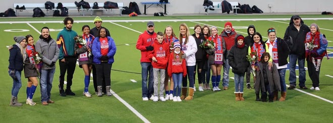 Heritage senior girls soccer players pose with family members as they are honored at last Tuesday's game against Life Waxahachie at MISD Multipurpose Stadium. The Jaguars routed Life, 10-1.