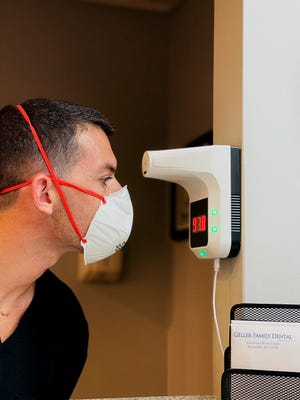 Dr. Andrew A. Geller, a general and cosmetic dentist at Geller Family Dental, has his temperature taken at the entry to his office on Thursday, Feb. 4, 2021, in Bronxville, New York. [Constantine Venetopoulos/Geller Family Dental via AP]