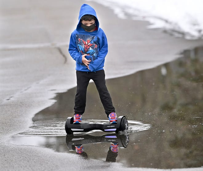 Monday night's ice became Tuesday's puddles as Kalleby Teles, 6, took his self-balancing hoverboard scooter through one at Cushing Memorial Park in Framingham, Feb. 16, 2021.
