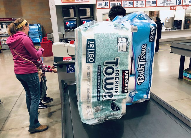 A shopper pays for packages of toilet paper and hand towels at a Costco warehouse in Lone Tree, Colorado. [AP File Photo/David Zalubowski]