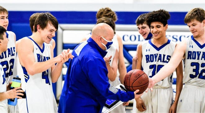 Colo-NESCO head boys' basketball coach received a signed basketball after picking up the 200th victory of his career when the Royals defeated Valley Lutheran, 63-25, during the Class 1A district play-in round Friday at Colo.