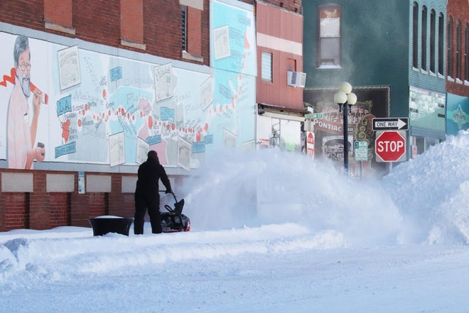 Seeing people clear sidewalks, like here on North Main Street near East Madison Street in Pontiac, was a common site in the area Tuesday morning after Monday's heavy snowfall. Unofficial totals of snowfall for Livingston County were 7-10 inches.