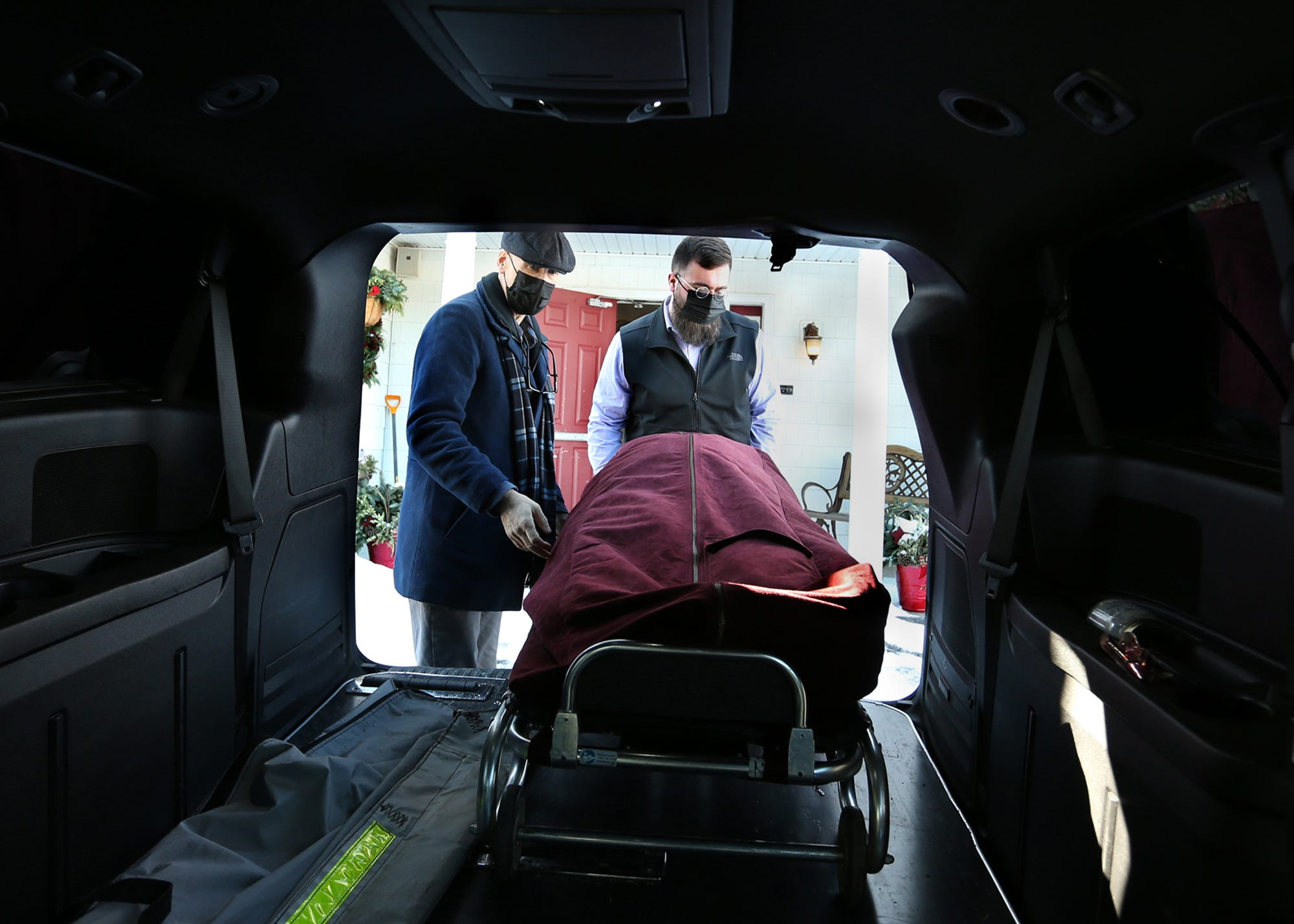 """After bringing a body into the care of J.S. Pelkey and Son Funeral, Jeff Pelkey, left, and Connor Martel gently remove the stretcher and bring the deceased individual through the front door of the funeral home. Pelkey says, """"People deserve to come in and out the front door. The front door is as important for the deceased as it is for the families."""""""