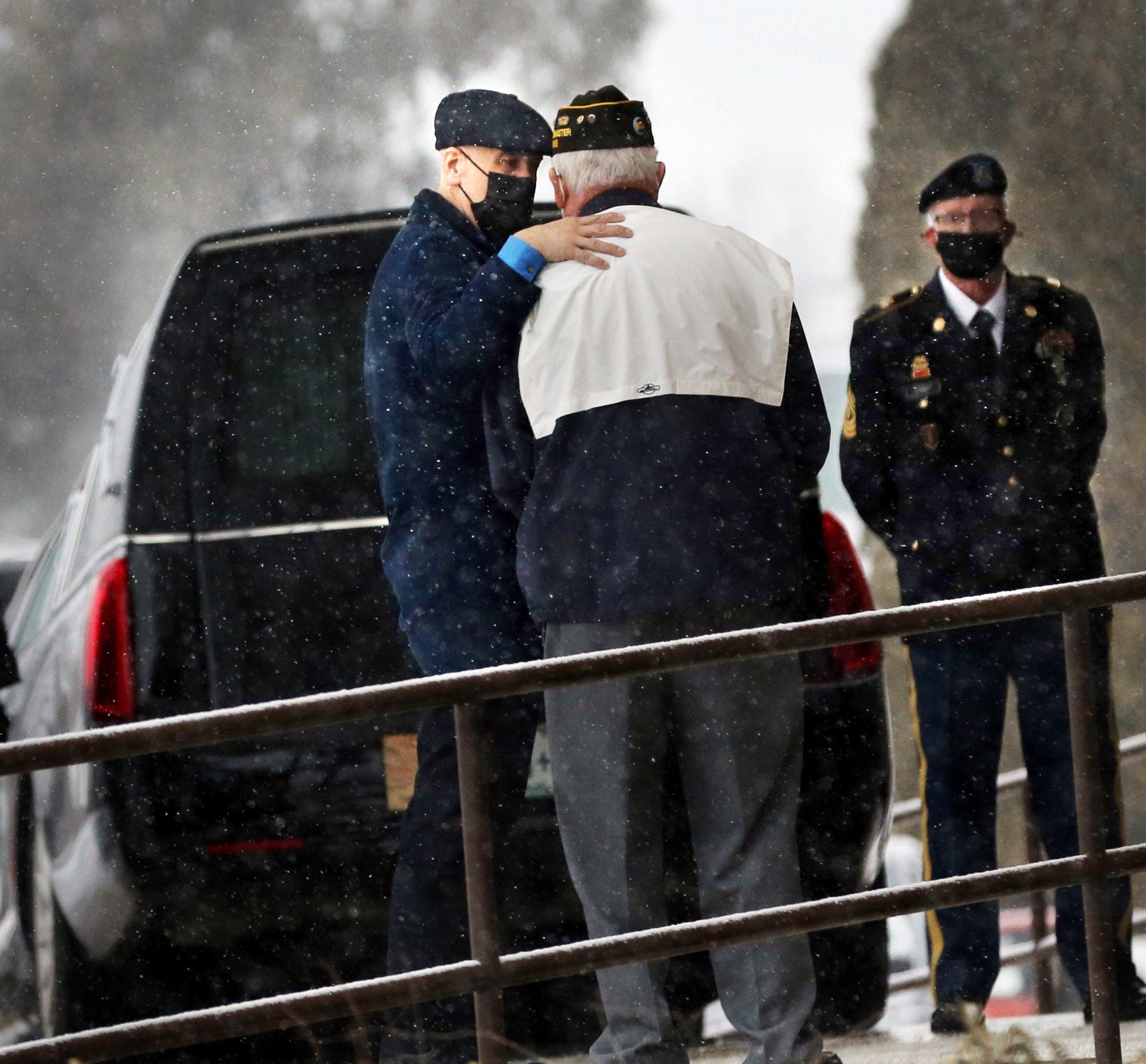 As snow falls gently, funeral home director Jeff Pelkey comforts a friend of the deceased during a funeral Mass. The gentleman, who was cremated, was a Korean War veteran who was heavily involved with the VFW.