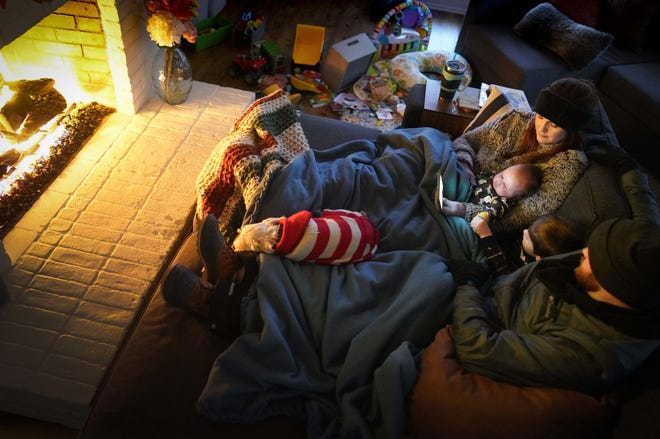 Dan Bryant and his wife Anna huddle by the fire with sons Benny, 3, and Sam, 12 weeks, along with their dog Joey, also wearing two doggie sweaters, with power out and temperatures dropping inside their home after a winter storm brought snow and freezing temperatures to North Texas on Monday, Feb. 15, 2021, in Garland, Texas.