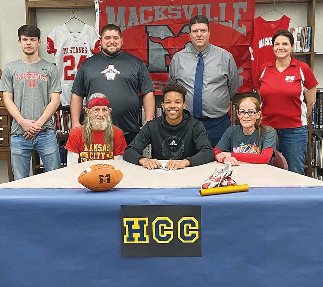 Backed by Macksville coaches and seated with his grandparents, Cleven Huggins, Macksville High School senior athlete, signs a letter of intent to play football and run track at Highlands Community College this fall.
