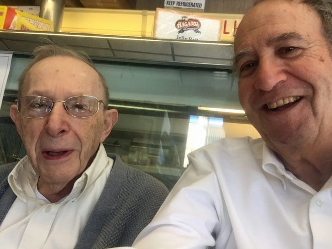 """Joslin """"Josh"""" Davis, left, with regular customer M. Charles Bakst, circa 2016, at Davis Dairy Products in Providence. The Jewish deli market, destroyed by a fire in May, will not reopen."""
