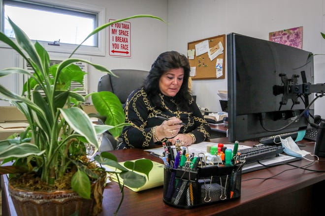 Sandy Leite, in her Warwick office, runs an employment agency that places workers with the state. She says the state owes her more  than $200,000 on invoices going back to July.